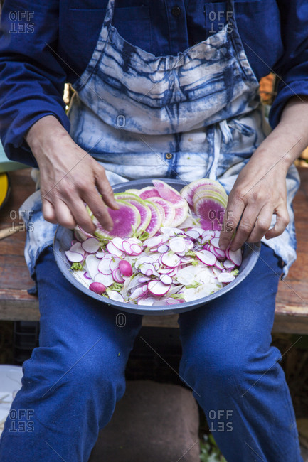 Woman holding plate of freshly sliced radishes