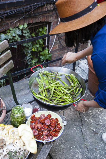 Woman cooking asparagus outdoors - Offset