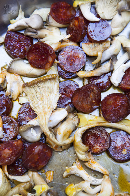 Close up of mushrooms and sausages being fried