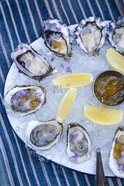 Oysters in a bowl with ice and lemon wedges