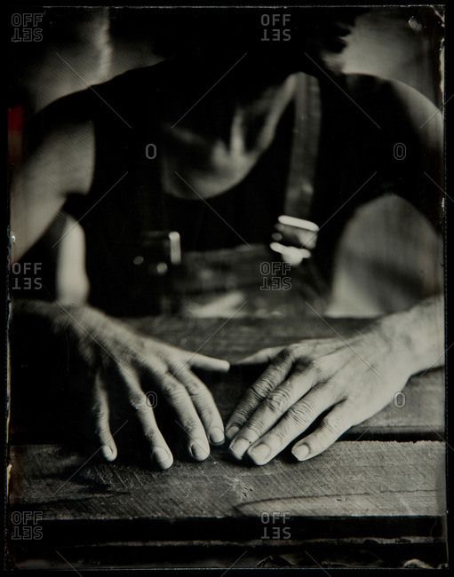 Woman's hand resting on wood table