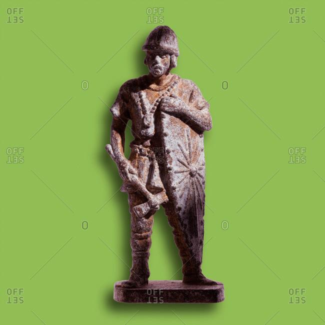 Medieval warrior figurine, green background