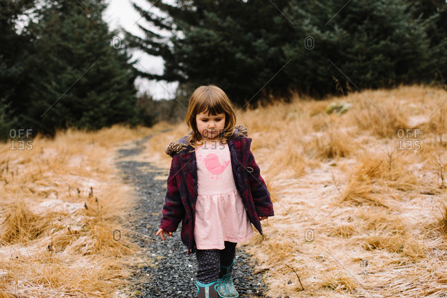Little girl walking on a footpath