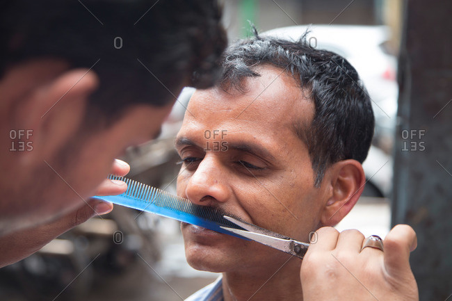 New Delhi, India - March 7, 2015: Man getting his mustache trimmed in the street in New Delhi, India