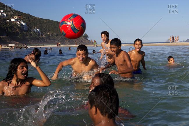 Rio de Janeiro, Brazil - July 7, 2010: Local youngsters play in the water on Sao Conrado beach