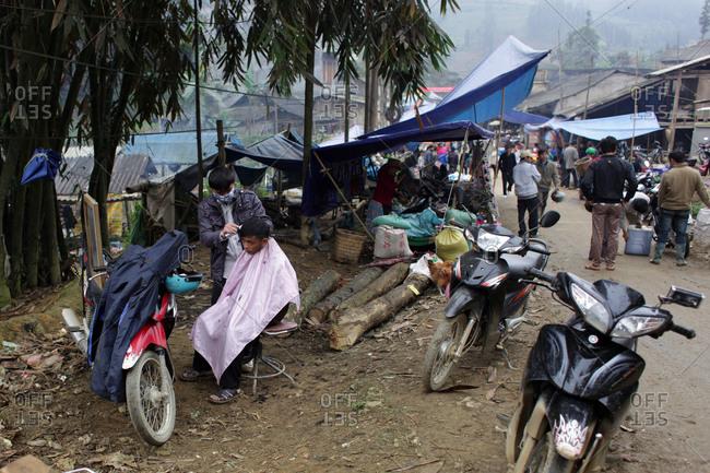 Lung Khau Nhin Market, Vietnam - March 15, 2012: A man receives a haircut at the Lung Khau Nhin Market
