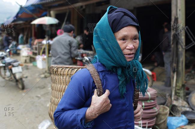 Lung Khau Nhin Market, Vietnam - March 15, 2012: A local woman with basket backpack at the rural tribal Lung Khau Nhin Market