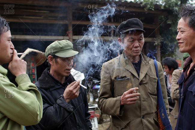 Lung Khau Nhin Market, Vietnam - March 15, 2012: Group of local men smoke and socialize at the Lung Khau Nhin Market in Northern Vietnam