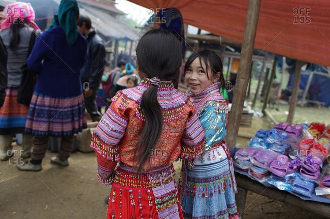 Lung Khau Nhin Market, Vietnam - March 15, 2012: Young Hmong girls in traditional beaded skirts at the Lung Khau Nhin Market