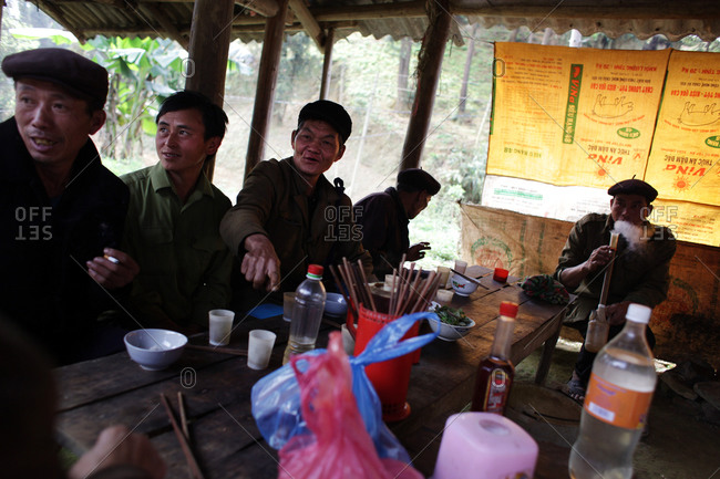 Lung Khau Nhin Market, Vietnam - March 15, 2012: Men drink and smoke at restaurant the Lung Khau Nhin Market