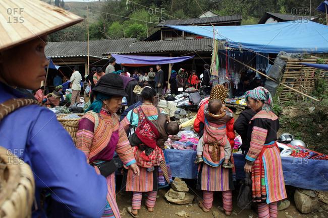 Lung Khau Nhin Market, Vietnam - March 15, 2012: Tribal women with babies on their backs shop for goods at Lung Khau Nhin Market