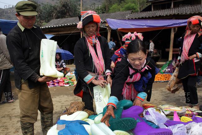 Lung Khau Nhin Market, Vietnam - March 15, 2012: Shoppers looking at waterproof boots at Lung Khau Nhin Market