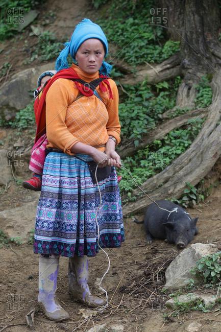Lung Khau Nhin Market, Vietnam - March 14, 2012: Woman with a pig on rope leash at Lung Khau Nhin Market