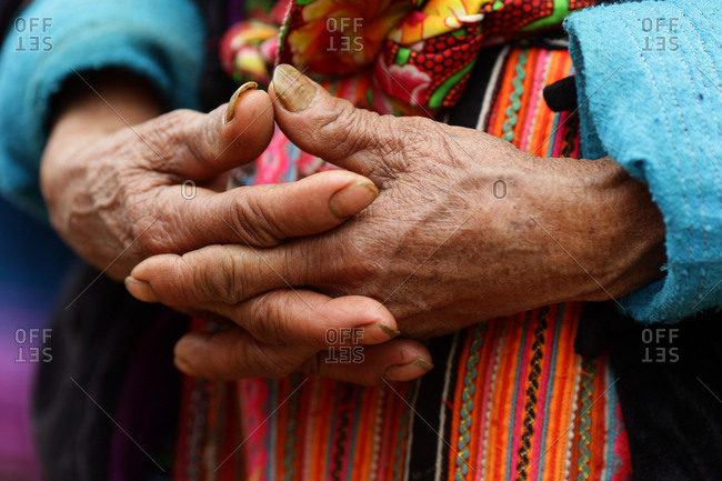 The hands of an elderly woman against her colorful skirt at the Lung Khau Nhin Market, Vietnam