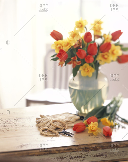 Tulips and daffodils in a vase on a rustic table