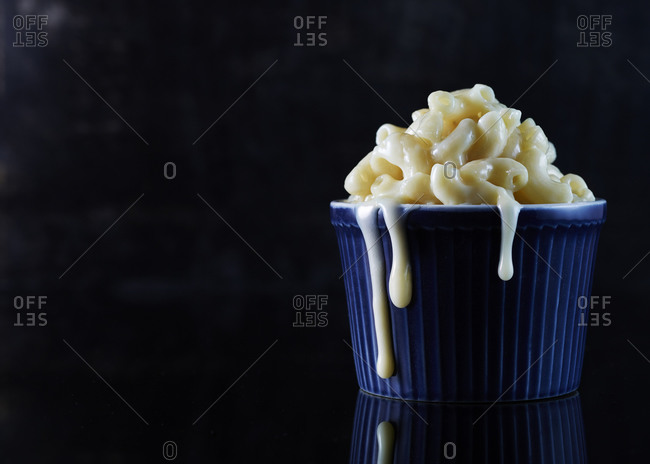 Macaroni and cheese oozing from a blue ceramic ramekin