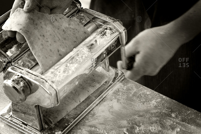 Man using a pasta machine to flatten dough