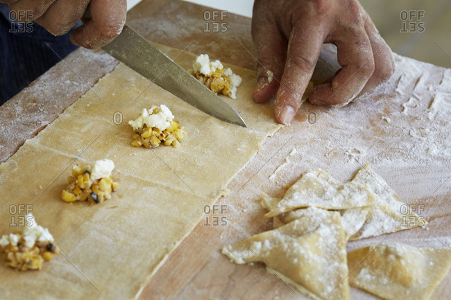 Man cutting dough for stuffed ravioli