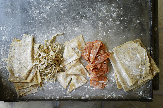 Different types of pasta on a floured metal surface