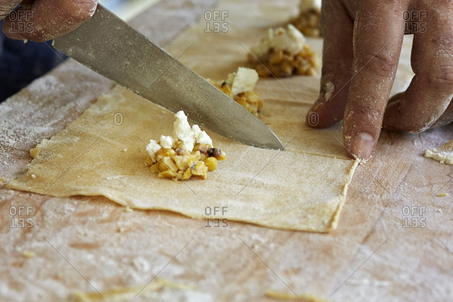 Man cutting individual pieces of ravioli from pasta dough