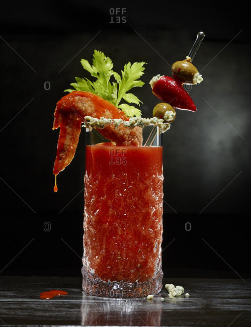 Bloody Mary garnished with a buffalo wing and stuffed olives