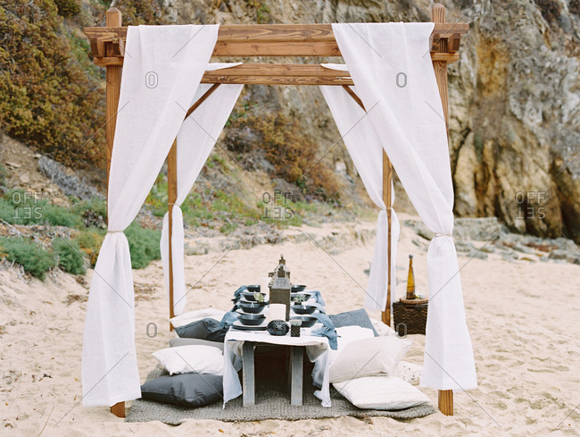 Table set under a pergola for a beach dinner party