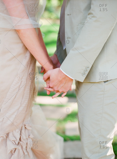 Newlywed couple holding hands on their wedding day