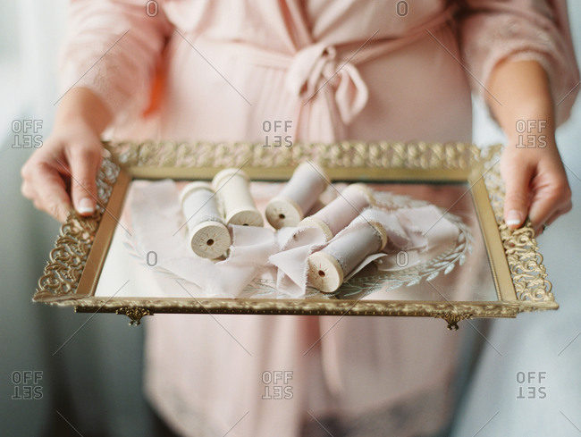 Woman holding spools of ribbon on a tray