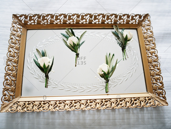White roses on a gold tray and mirror