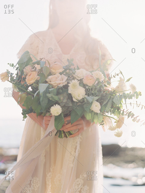 Bride holding bouquet of flowers on a sunny day