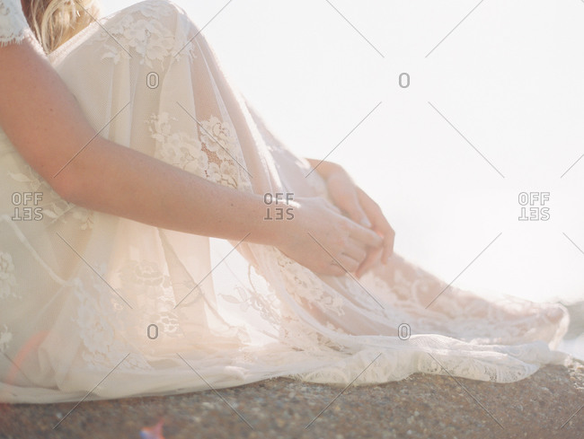 Bride sitting on the beach on a sunny day