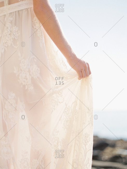Bride lifting the skirt of her wedding dress of the ground