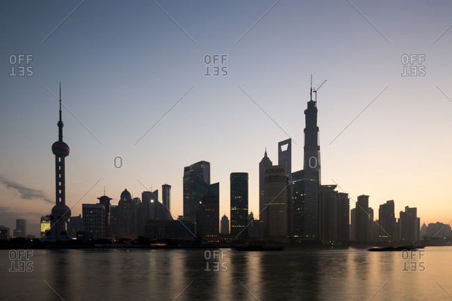 Glow of twilight behind towering skyline of Pudong district along Huangpu River on autumn morning