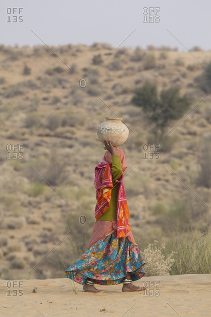 Colorfully dressed village woman walking with pot on her head, going to village well