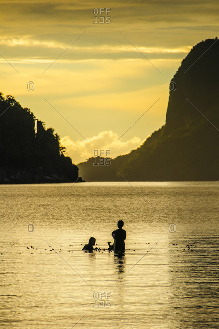 Young boys fishing at sunset in the bay of El Nido, Bacuit Archipelago, Palawan, Philippines