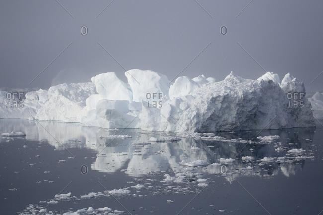 Iceberg in sea and mist from glacier Sermeq Kujalleq, Ilulissat, Greenland