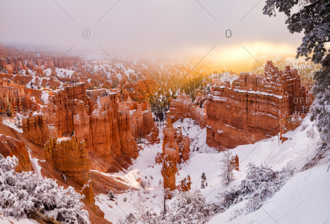 Bryce Canyon National Park Panoramic view of sunrise peeking through the fog and clouds