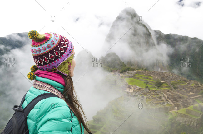 Woman enjoying Machu Picchu before sunrise with the ruins surrounded by fog