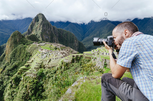 Man taking pictures of Machu Picchu citadel and Huayna Picchu mountain