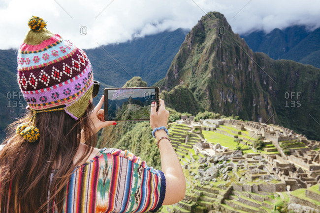 Woman taking pictures of Machu Picchu citadel and Huayna Picchu mountain with a tablet