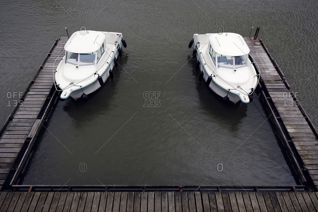 Two similar motor yachts moored at jetty of Media Harbour