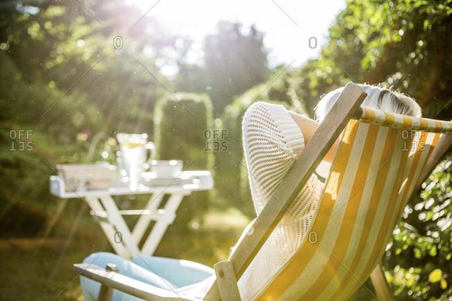 Mature woman relaxing in deckchair in garden