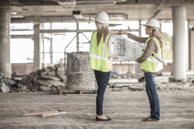 Two women in protective workwear discussing building plan in construction site