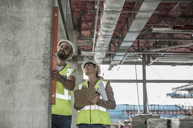 Woman with construction worker using water level in construction site