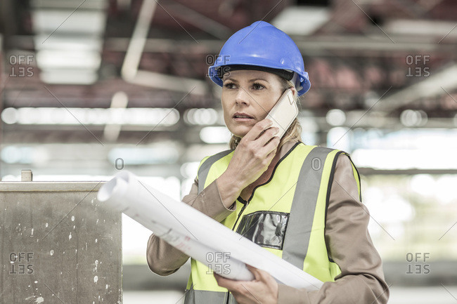 Woman in protective workwear on cell phone in construction site