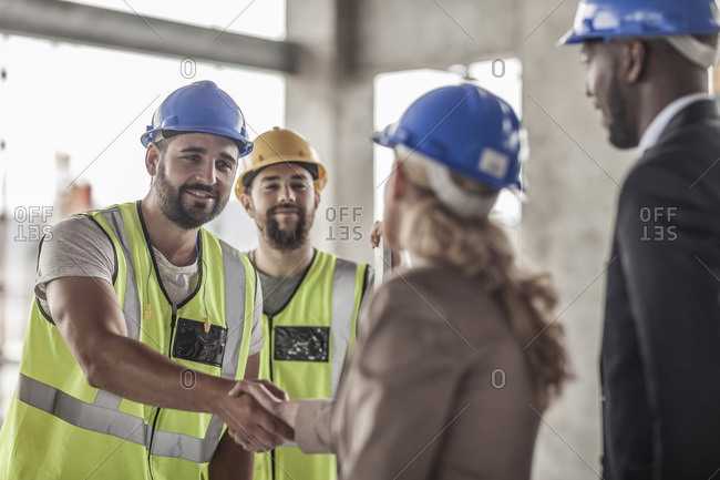 Construction worker and executive shaking hands in construction site