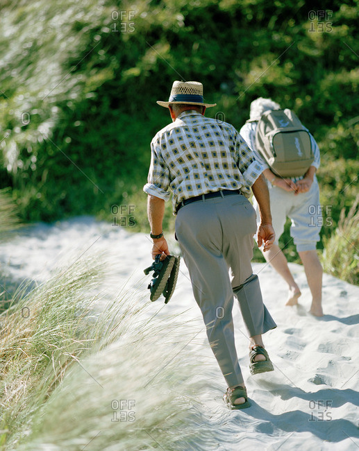 Elderly couple wandering through sand dunes towards Wharariki Beach, Northwest coast, South Island, New Zealand