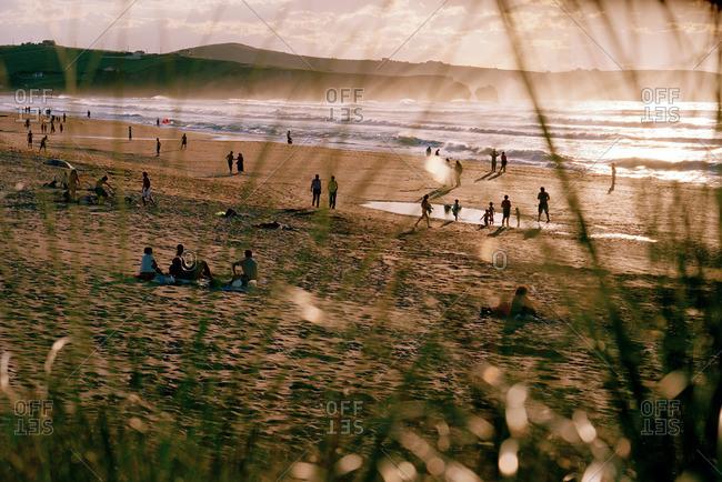 Sunbathers on the beach at sunset, Playa de Valdearenas, west of Santander, Cantabria, Spain