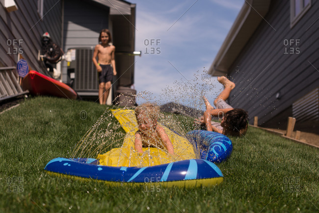 Boy sliding down a backyard water slide sprinkler