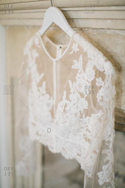 A lace wedding bolero shrug hanging on a mantle